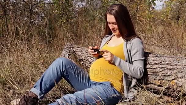 Těhotná žena používá její smartphone sedí v parku