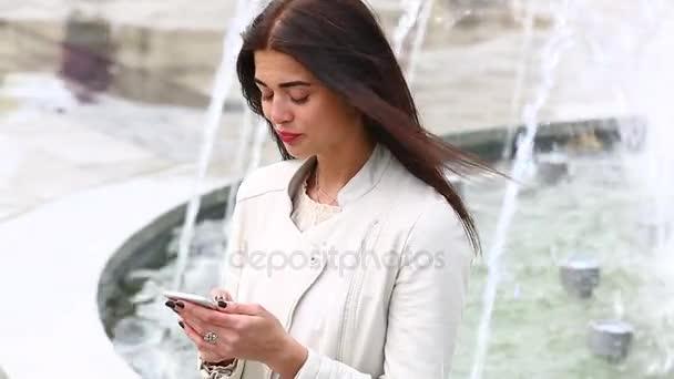 Porträt eines Mädchens Lachen mit Smartphone. Hübsche junge Frau mit ihrem Handy auf Brunnen Hintergrund. Sehr zufrieden Frau mit Smartphone im Stadtpark, Steadicam erschossen.