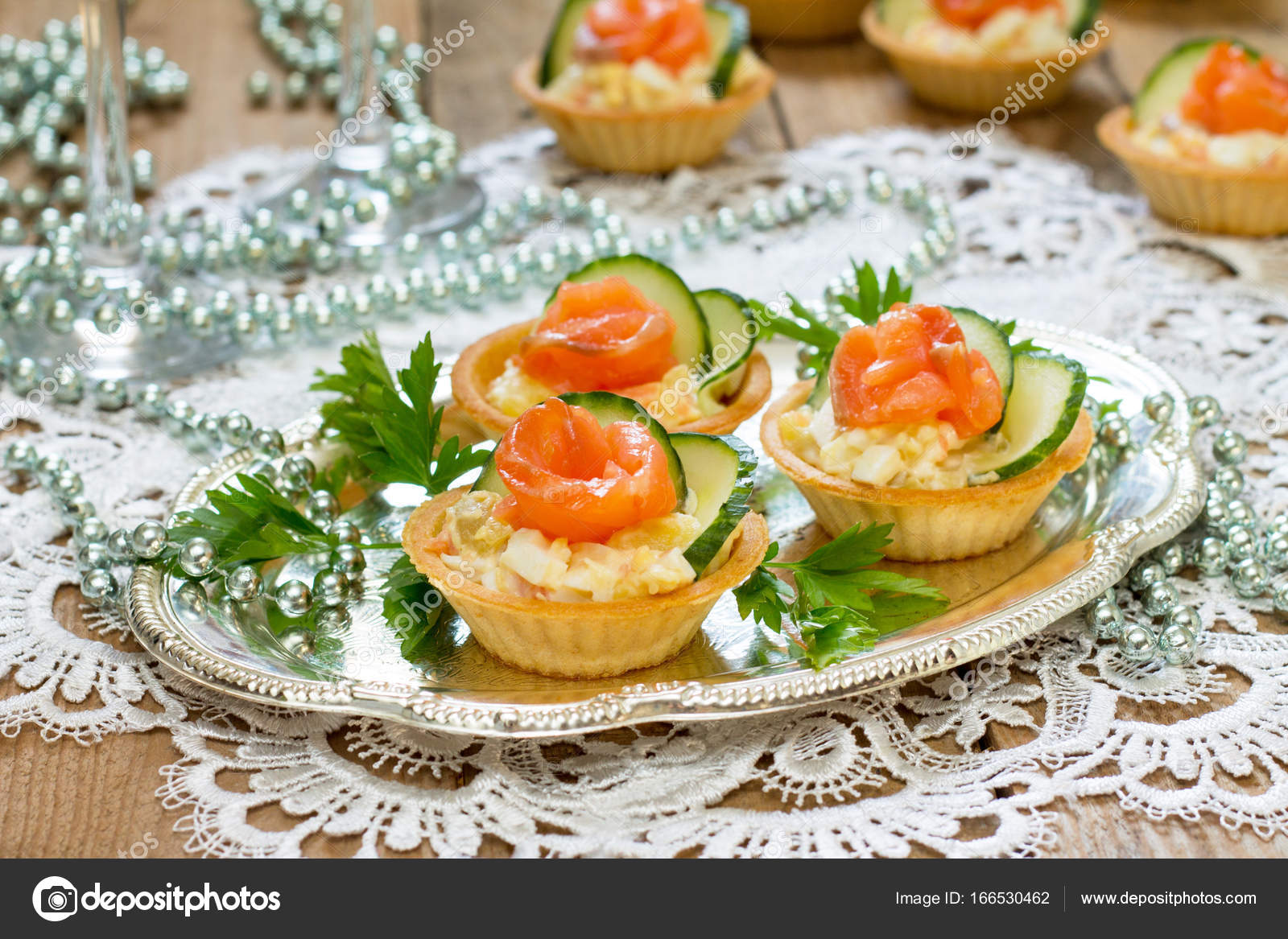 Christmas snack on the festive table. Tartlets with salad, decor ...