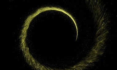 Gold glittering spiral trail of sparkling dust particles on black background.