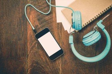 Top view note paper,headphones,smartphone,pencil,on wooden offic