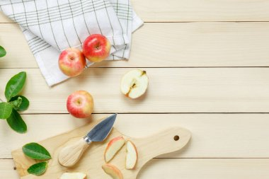 Top view red apple sliced,knife,napkin, leaf on wooden.