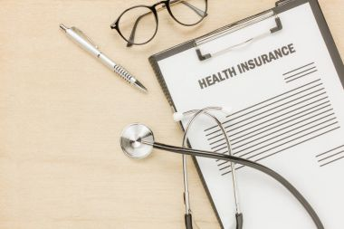 Top view health insurance form and eyeglasses with stethoscope.