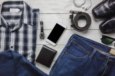 Top view / Flat lay accessoires to travel and technology with man / gentlemen clothing on white wooden table