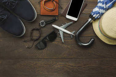 Aerial view of items to travel with technology background concept. Accessories  traveler teenage or adult man for vacation.Essential mix variety object on modern rustic brown wood office desk.