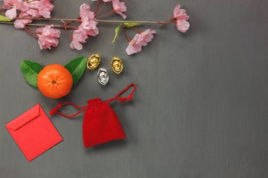 Above view of decorations Chinese & lunar New Year concept backgrounds.many objects is sign of the season.items on classic grey grunge home table.Other language means wealthy or rich and happiness.