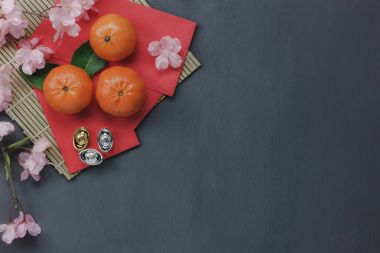 Aerial view of decorations Chinese & lunar New Year concept background.Mix items and oranges on classic grey grunge home office table.Other language means wealthy or rich and happiness.space for font.