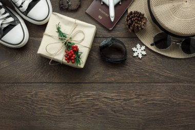 Above view of ornaments and decorations Merry Christmas and Happy New Year with accessory to travel concept background.several sign item on modern rustic home office desk.space to creative design text