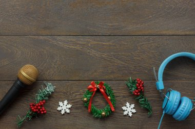Above view of ornaments & decorations Happy new year and Merry Christmas with music concept.Mix objects composition on the modern rustic brown wooden at home office desk.Free space for creative font.