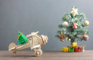 Toy wood airplane transfer fir tree with Blur Christmas tree & many beautiful gift box also essential decoration accessory.Variety objects on modern rustic brown wooden plank and blur grey background.