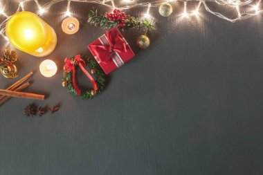 Table top view image of Christmas decoration & Ornament Happy new year background concept.Lighting & Candle withe essential items for season on modern grunge grey wooden at home office desk with space