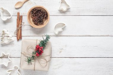 Above view image of Merry Christmas & Happy new year background concept.Accessories for make dessert with gift box & fir tree on white wooden at home office desk.Free space for creative design text.