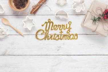 Table top view aerial image of Gold Merry Christmas text with cooking accessories.All idea for make dessert for winter season.Many difference object on white wooden at home office desk background.