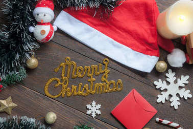 Table top view image of Merry Christmas text with decoration & ornament for winter season.Many difference decor on modern brown rustic wooden at home office desk studio.Christmas and new year concept