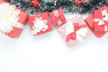 Above view aerial image of many gift box with fir tree.Merry Christmas & decoration happy new year background concept.Table top beautiful accessories objects on white backdrop at home office desk.