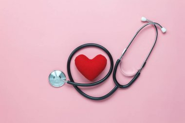 Table top view shot of arrangement equipment medical background concept.Red heart & stethoscope on modern rustic pink paper.An idea essential accessories for doctor for  care patient  in hospital.