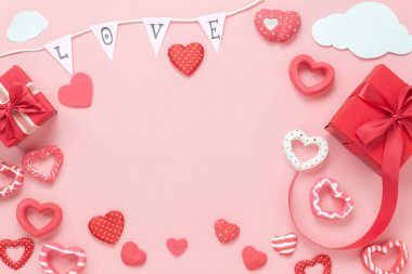 Table top view image of decoration valentine's day background concept.Flat lay arrangement of red shape & gift box with essential items on modern rustic pink paper with middle space for mock up design