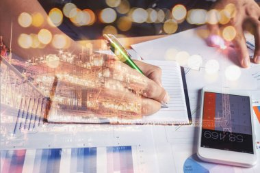 Close up business man calculate accounting & finance graph document with mobile phone calculator on office desk.Double exposure chart growth up & financial concept with offshore oil & gas platform.