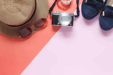 Table top view accessory of clothing women plan to travel in holiday background.Beauty & Fashion concept.Flat lay of camera with many essential items costume and sun glasses on modern pink paper.