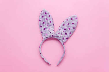 Top view aerial image of decorations & symbol Happy Easter holiday background concept.Flat lay accessory costume for festive purple bunny ear on modern grunge pink paper backdrop at home office desk.