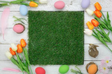 Table top view shot of decorations Happy Easter holiday background concept.Flat lay bunny eggs with tulip flower on modern rustic white at office desk.Blank space at green grass design for mock up.