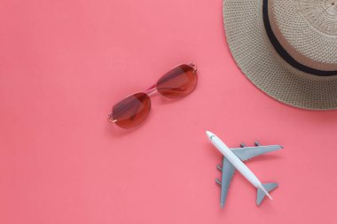 Table top view accessory of accessory travel in holiday background concept.Flat lay of airplane & sunglasses with hat on modern rustic pink paper at home studio office desk.copy space for creative.