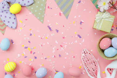 Table top view shot of arrangement decoration Happy Easter holiday background concept.Flat lay colorful bunny egg with accessory to celebration on modern rustic pink pastel paper at home office desk.