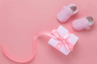 Top view aerial image of decoration Happy mothers day holiday background concept.Flat lay gift box with baby shoes on modern beautiful pink paper at home office desk.Free space for creative design.