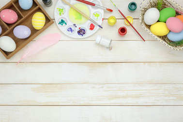 Table top view shot of arrangement decoration Happy Easter holiday background concept.Flat lay colorful bunny egg with item to painting activity on modern rustic white wooden at home office desk.
