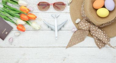 Table top view shot of decoration Happy Easter holiday background concept.Flat lay essential women objects plan to travel vacation on modern white wooden at office desk.Accessory for traveler to trip.