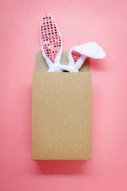Table top view aerial image of decoration & symbol Happy Easter holiday background concept.Flat lay accessory costume bunny ear with paper bag on modern beautiful pink paper at home office desk.