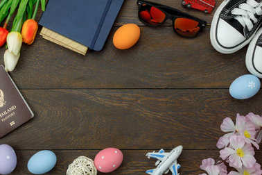 Top view shot of arrangement decoration Happy Easter holiday background concept.Flat lay colorful Easter egg with tulip flower and rabbit bunny on modern brown wooden at office desk.space for mock up