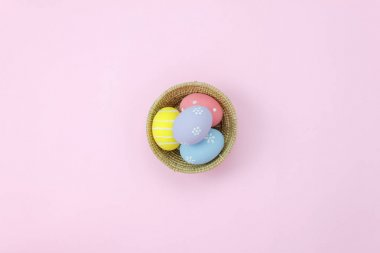 Table top view shot of arrangement decoration Happy Easter holiday background concept.Flat lay essential colorful bunny egg on modern rustic pink paper at home office desk.Space for creative design.