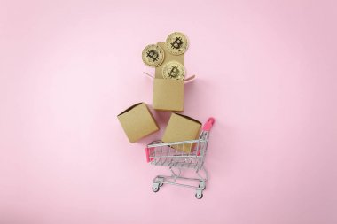 Table top view aerial image of business finance background.Flat lay graph growth up with coin money & shopping cart or trolley on modern pink paper.Sale marketing concept.Space for creative design.