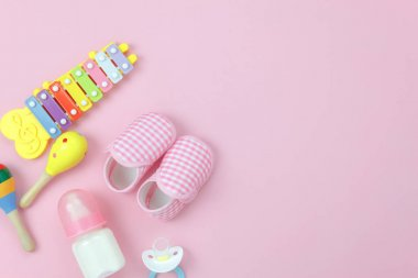 Table top view image the kids toys for development background concept.Flat lay accessory objects for children on modern rustic pink at home office desk.Design pastel tone with copy space for add text.