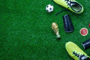Table top view of soccer or football world cup season background.Flat lay accessories trophy & ball with shoe on the artificial green grass wallpaper.Free space for creative design text and content.