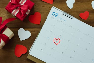 Table top view aerial image of decoration valentine's day background concept.Flat lay arrangement of calendar page of february month with essential items love heart with gift box on wooden.