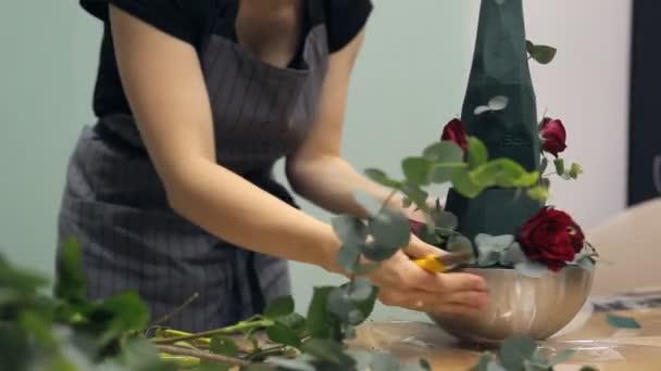 Květinářství vytváří svěží květinové aranžmá s růžemi a eukalyptus