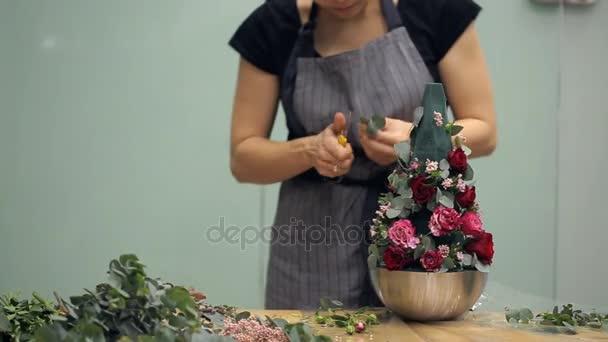 Květinářství pracuje s květinovým složením vysvětluje technika na stole uvnitř