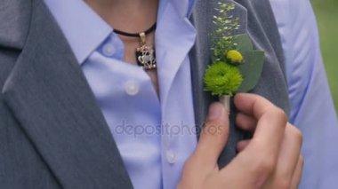 Muž v obleku opravuje malé ženicha kytice na závoj na svatební den
