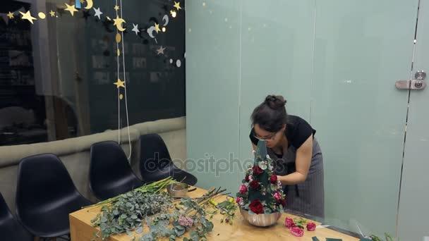 Brunetka květinářství dělá aranžmá na stole v kanceláři