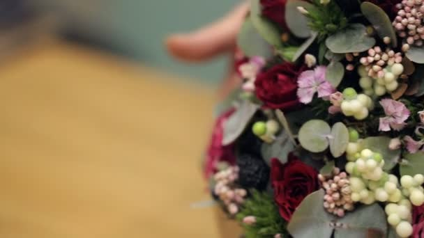 Květinářství ukazuje dokončené květinové aranžmá na stole v kanceláři