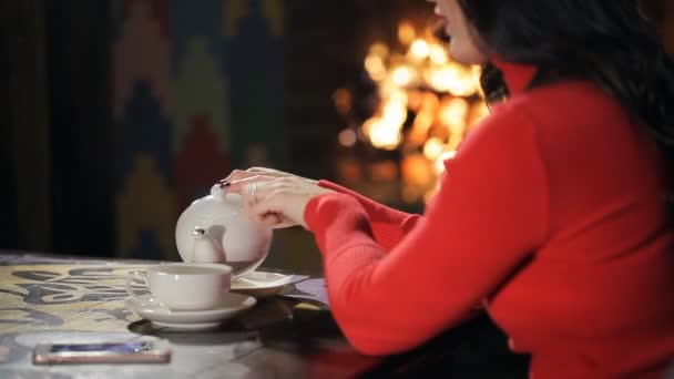 Woman in red gives some tea against background of burning fireplace.