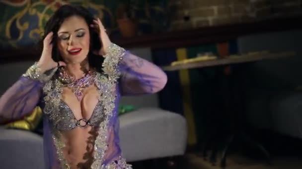 Bruneta žena v lila kostým tance břišní tanec na podlaze