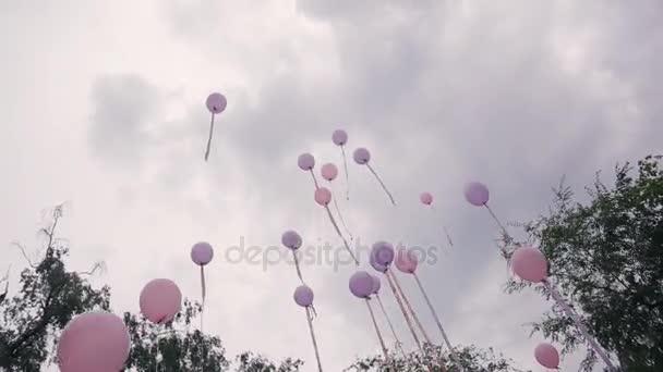 Mnoho růžové fialové balonky letět do nebe v den svatby venku