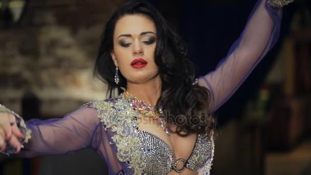 Bruneta-tanečnice tančí, při pohledu do kamery uvnitř restaurace