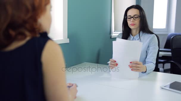 Beautiful brunette gives documents to charming girl opposite.
