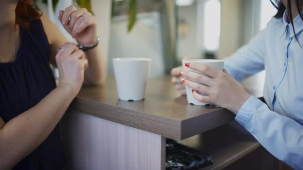 Close up hands of two office-workers drinking tea inside office