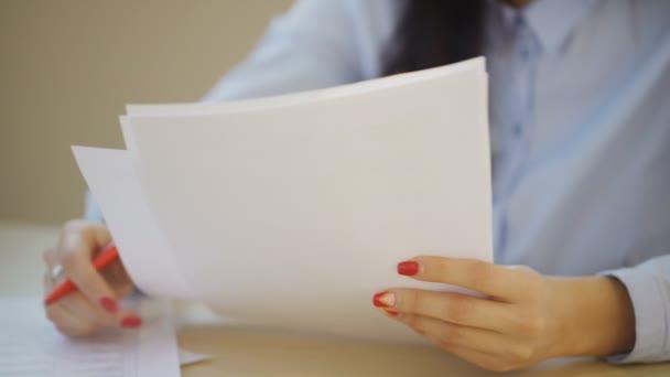 Detailní záběr žena ruce psaní, vyplňování listy papíru uvnitř úřadu