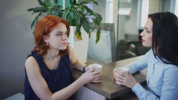 Dvě mladé krásné ženy popovídat při šálku kávy v kanceláři